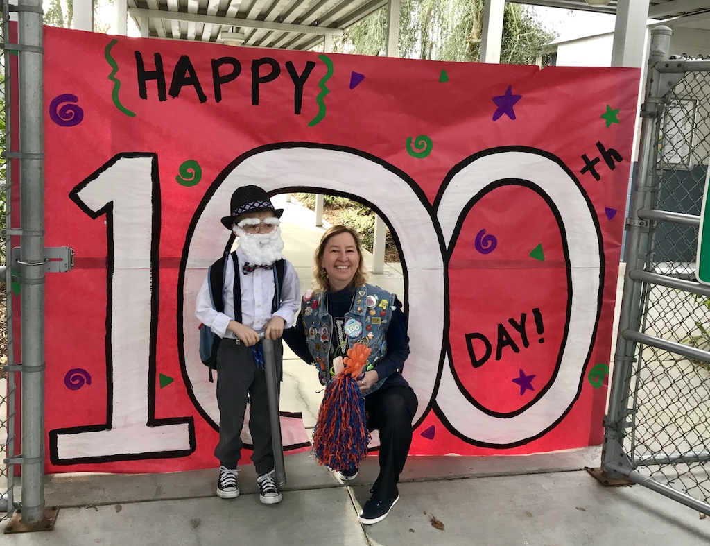 Sand Pine Elementary principal Christina Twardosz and a student celebrate the 100th Day of school.
