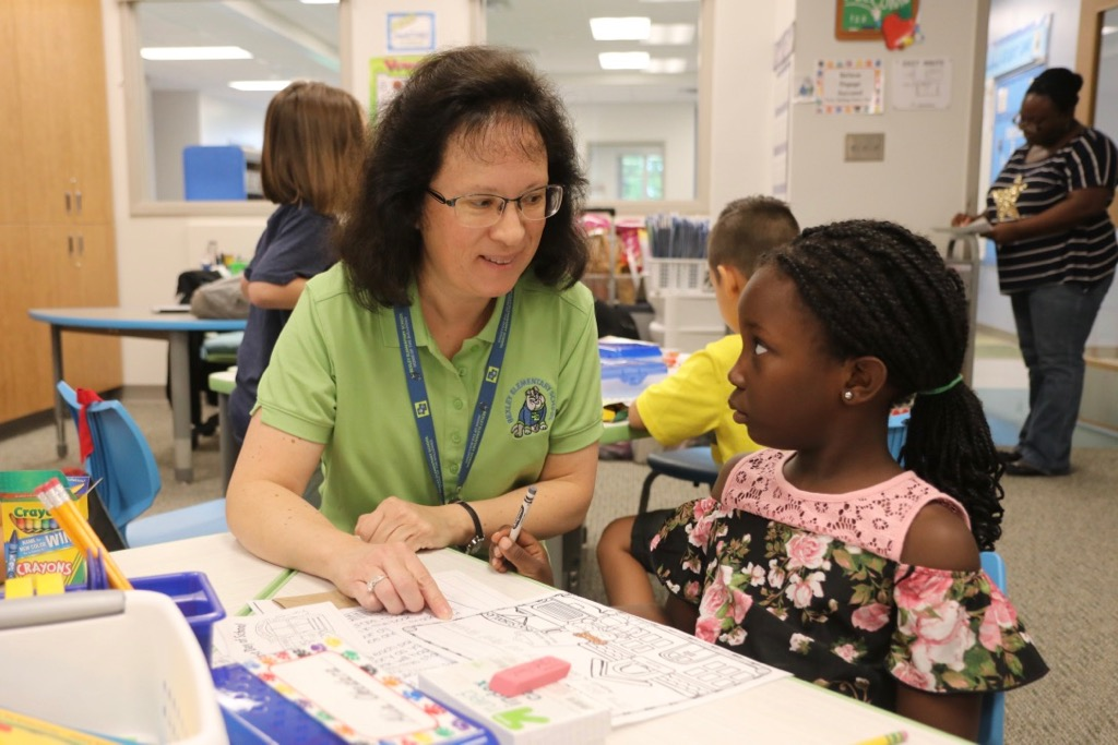 Bexley Elementary teacher Maureen Gerbin works with a student on the first day of school.